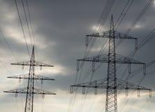 Pilões da eletricidade contra nuvens escuras Foto de Stock