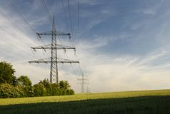 Pilões da eletricidade na paisagem verde foto de stock