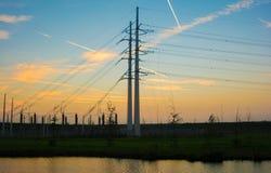 Pilões da eletricidade no campo da cevada Fotos de Stock