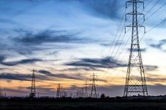 Pilões da eletricidade no por do sol fotografia de stock