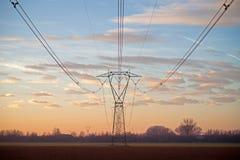 Pilões da eletricidade no por do sol Fotos de Stock