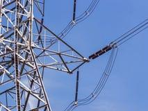 Pilões de alta tensão do poder contra o céu azul Imagem de Stock Royalty Free