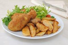 Pilões de galinha com côdeas de pão ralado com batatas e salada imagem de stock royalty free