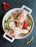 Pilões de galinha crus com as especiarias no prato branco do cozimento na placa de pedra preta, vista superior foto de stock royalty free