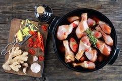 Pilões de galinha crus no potenciômetro preto foto de stock royalty free