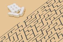 Pil av preventivpillerar tillsammans med en labyrint Arkivfoto