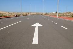 Pil på en asfaltgata till framtiden Arkivbilder
