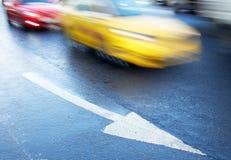 Pil på vägen och de rörande bilarna royaltyfria foton