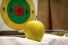 Pil som trängas igenom till och med det gröna äpplet mot bakgrunden av målet arkivbild