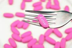Pil van liefde op een vork Roze pil Stock Foto's