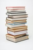 Pila alta de libros en el fondo blanco. Imagenes de archivo