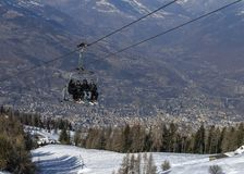 Four middle aged men skiers take a chair lift up the mountain at Pila ski resort in Aosta Valley, Italy. City of Aosta in backgrou royalty free stock image