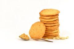 Pila aseada de galletas de mantequilla hechas en casa de cacahuete con una que descansa contra él, peanurs dispersados y mantequi imagen de archivo
