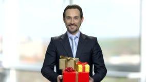 Pila atractiva de la tenencia del hombre de negocios de cajas de regalo almacen de metraje de vídeo