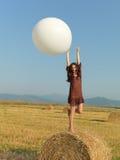 Pila blanca de salto del heno del globo de la mujer feliz Imágenes de archivo libres de regalías