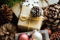 Pila cajas de regalo de la Navidad y del Año Nuevo envueltas en papel marrón del arte, conos del pino, ramas de árbol de abeto, c Imagenes de archivo