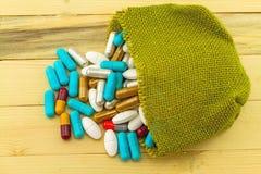 Pila colorida de las píldoras en sisal verde del saco en de madera marrón Fotos de archivo