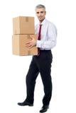 Pila corporativa della tenuta dell'uomo di scatole del pacchetto fotografia stock libera da diritti