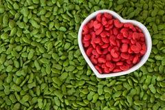 Pila de alimento para animales seco con el color rojo en taza del corazón, concepto del animal doméstico del amor Imagen de archivo