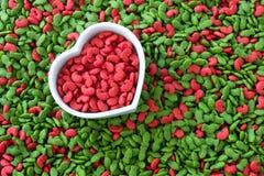 Pila de alimento para animales seco con el color rojo en taza del corazón, concepto del animal doméstico del amor Fotografía de archivo
