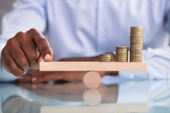 Pila de Balancing The Coin del hombre de negocios en la oscilaci?n de madera imagen de archivo