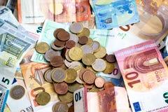 Pila de billetes de banco y de monedas euro fotos de archivo