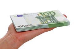 Pila de 100 billetes de banco euro en la palma Imagen de archivo libre de regalías