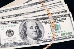 Pila de 100 billetes de dólar y joyerías del oro en un backgr azul marino Imagen de archivo