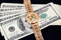 Pila de 100 billetes de dólar y relojes de oro en un fondo oscuro Foto de archivo libre de regalías