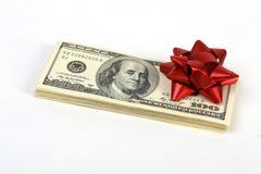 Pila de billetes de dólar del americano ciento del dinero con el arco rojo Imagen de archivo libre de regalías