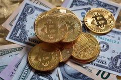 Pila de Bitcoins en fondo de los billetes de banco del dólar Foto de archivo libre de regalías
