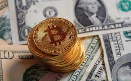 Pila de Bitcoins en fondo de los billetes de banco del dólar Fotos de archivo libres de regalías
