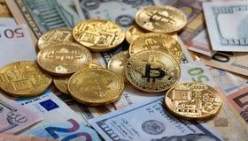 Pila de Bitcoins en fondo de los billetes de banco del dólar y del euro Fotografía de archivo libre de regalías