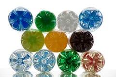 Pila de botellas plásticas del color en el fondo blanco Imagen de archivo