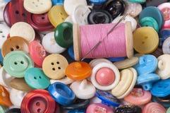 Pila de botones coloreados viejos con el hilo y la aguja Foto de archivo