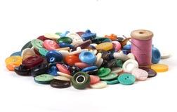 Pila de botones coloreados viejos con el hilo y la aguja en la parte posterior del blanco Fotografía de archivo
