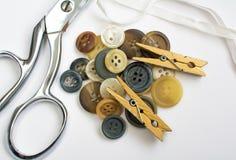 Pila de botones con los materiales de costura aislados en blanco Fotos de archivo libres de regalías