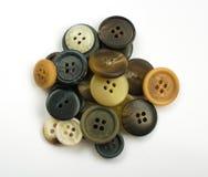 Pila de botones oscuros clasificados aislados en blanco Imagen de archivo libre de regalías