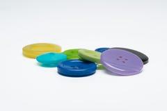 Pila de botones plásticos de costura coloridos en el fondo blanco Imagenes de archivo