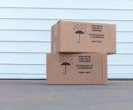 Pila de cajas de cartón sobre el fondo blanco de la puerta del almacén Imagen de archivo libre de regalías