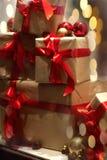 Pila de cajas de regalo envueltas en papel del arte con las cintas rojas en b imagenes de archivo