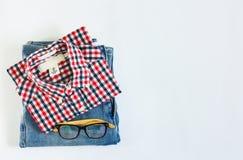Pila de camisa de tela escocesa y de mezclilla azul con los vidrios en el fondo blanco imagenes de archivo