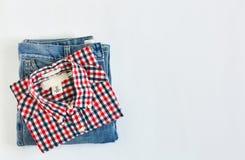 Pila de camisa de tela escocesa y de mezclilla azul en el fondo blanco fotografía de archivo libre de regalías