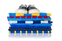 Pila de camisas coloridas del verano y un par de zapatillas de deporte en el top i Imagen de archivo