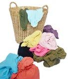 Pila de camisas coloridas en una cesta de mimbre fotos de archivo