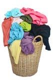 Pila de camisas coloridas en una cesta de mimbre, backg blanco aislado foto de archivo
