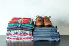Pila de camisas coloridas, de vaqueros y de zapatos en la tabla contra fondo ligero foto de archivo
