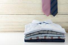 Pila de camisas de los hombres con el lazo Fotografía de archivo libre de regalías