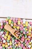 Pila de caramelos redondos coloridos con la cuchara de madera Imagen de archivo
