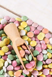 Pila de caramelos redondos coloridos con la cuchara de madera Imagenes de archivo